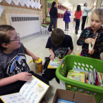 Third-graders, from left, Collin Harvey, Bayne Altenburg and Aliyah Morrison clean donated books at Adams School. The youngsters are part of a group of kids at the school involved in a project that provides gently used books to families to use for reading.